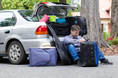 chobot: Bezmocný otec vedle kufru auta, horizontální