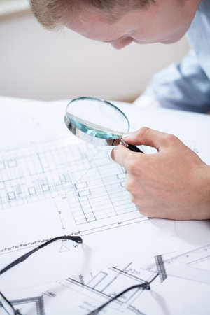 finacial: Young engineer analyzing the plan of the new construction in his office