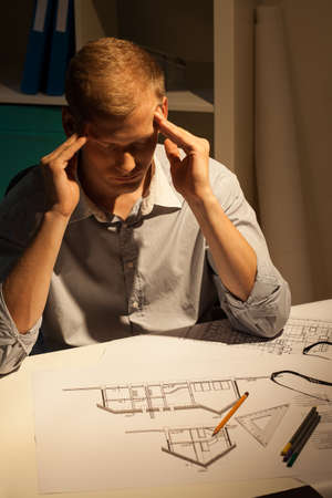 Young tired architect thinking about new project late at work in his office photo