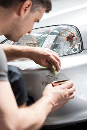 repair: Man removing scratches from car bumper, vertical Stock Photo
