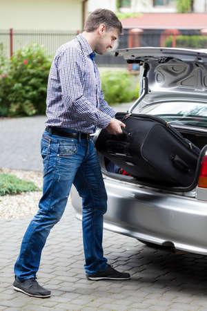 Man brengen de bagage in de auto kofferbak, verticale Stockfoto