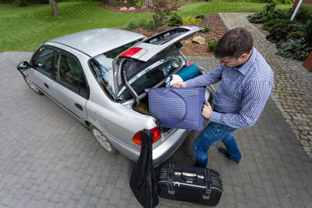 Man preparing car trunk for a trip photo