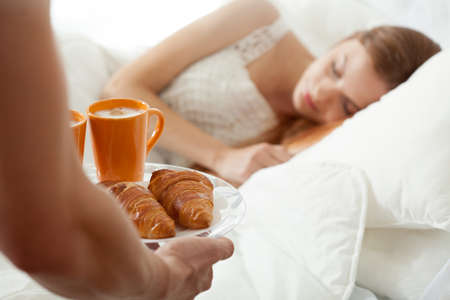 Surprise breakfast for sleeping woman in bed