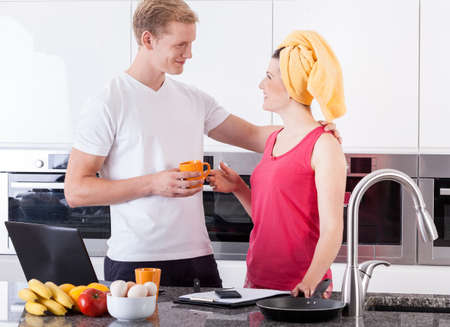 family kitchen: Busy couple during quick breakfast in the kitchen Stock Photo