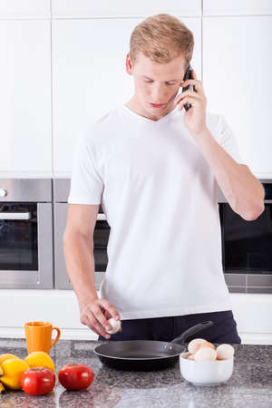 Man preparing scrambled eggs and calling on mobile phone photo