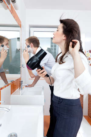 couple bathroom: Young couple preparing in front of the mirror in bathroom Stock Photo