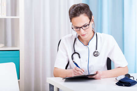 Doctor being busy working in her office photo