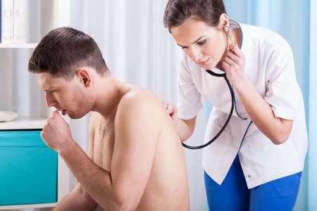 tosiendo: Vista horizontal de toser hombre que tiene examinación Foto de archivo