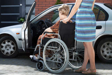 Girl helping senior woman on wheelchair getting into a car, horizontal