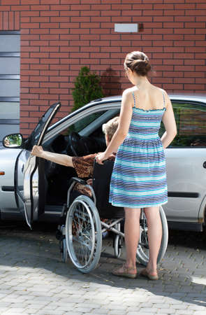 Disabled senior female driver and caregiver, vertical photo