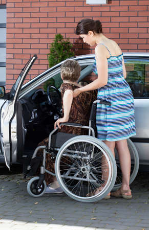 Young girl assisting senior disabled woman getting into a car photo