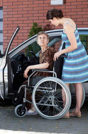 silla de ruedas: Conductor de sexo femenino mayor en silla de ruedas y una mujer joven