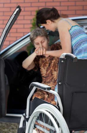 transportes: Chica para ayudar a personas con discapacidad mujer mayor que sale del coche Foto de archivo