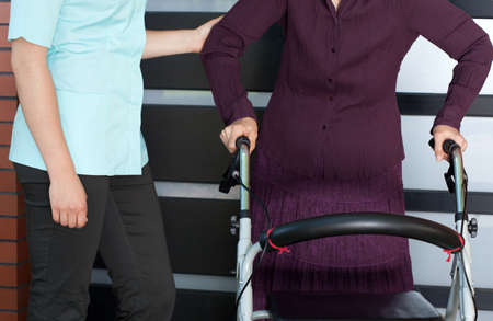 Close-up of a senior woman with orthopedic walker and nurse photo