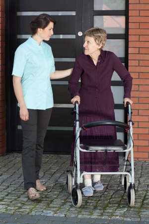 Female doctor assisting an old woman with her walker outdoors photo