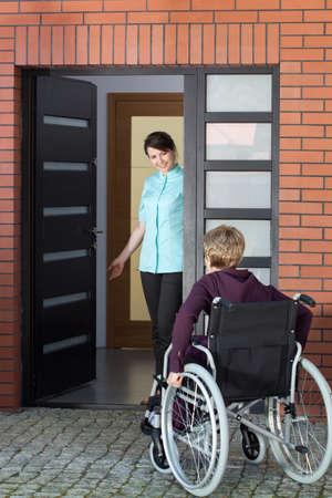 Vrouwelijke verzorger uitnodigende bejaarde vrouw op rolstoel naar verpleeghuis