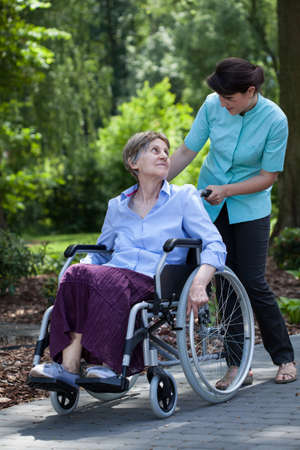 mobility nursing: Disabled senior woman walking with young nurse in park