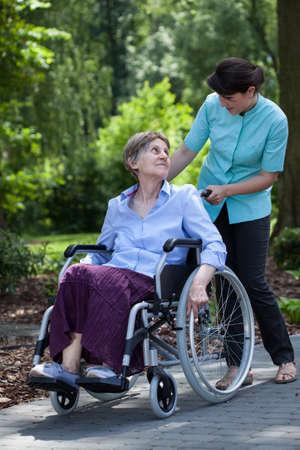 fisioterapia: Discapacitados altos mujer caminando con los j�venes enfermera en el parque