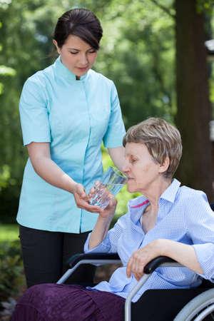 vaso de agua: Inicio cuidador dando vaso de agua a la mujer mayor Foto de archivo