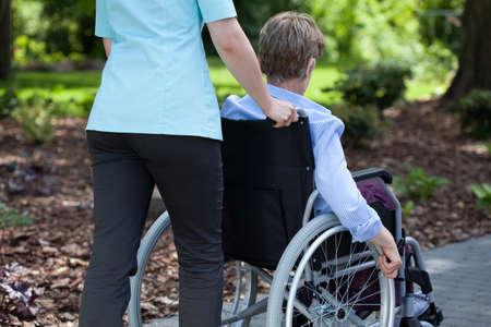 Close-up van een verpleegster duwen bejaarde vrouw op rolstoel