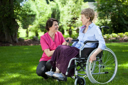 Happy senior woman on wheelchair with caring caregiver outdoors