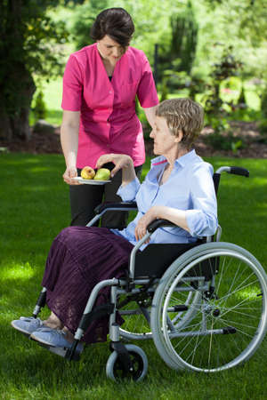 Caregiver giving fresh and healthy pear to disabled senior woman photo