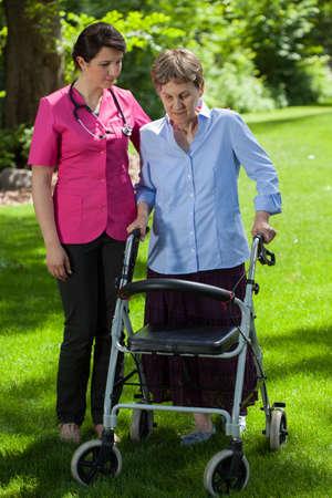 Female nurse walking beside senior woman with orthopedic walker photo