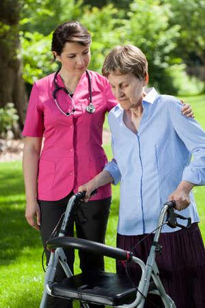 Female physiotherapist looking at elderly woman using orthopedic walker photo