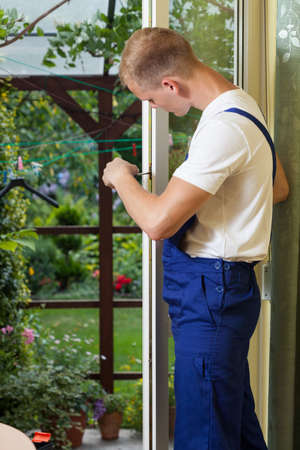 Young man repairing a terrace door with a screwdriver photo
