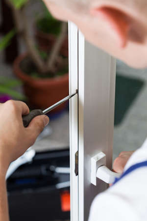 Repairman adjusting a bolt on terrace door with screwdriver photo