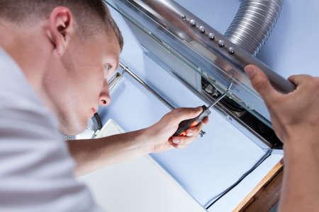 Jonge klusjesman vaststelling van een keuken afzuigkap met een schroevendraaier
