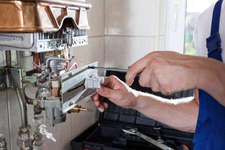 fontanero: Reparador fijaci�n de un calentador de agua de gas con un destornillador