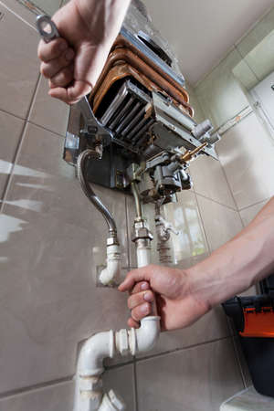 hot water: Plumber mending a gas water heater with a wrench