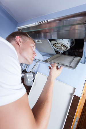 stove pipe: Young repairman fixing a broken kitchen extractor fan