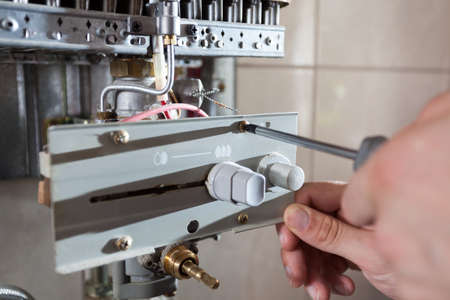 Plumber fixing a gas water heater with screwdriver photo