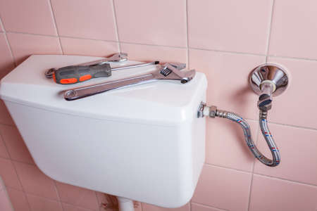 cistern: Wrench spanner and screwdiver lying on a toilet Stock Photo
