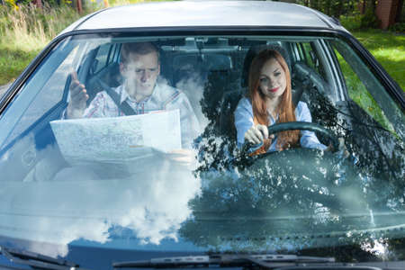 navigate: Man with map navigating woman in car Stock Photo