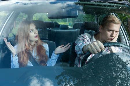 pareja enojada: Hombre aburrido en un coche escuchando esposa Foto de archivo