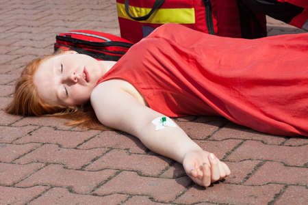 senseless: Unconscious girl with intravenous cannula in her arm Stock Photo