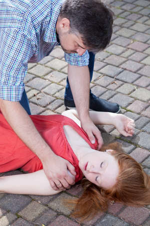 unconscious: Man checking up consciousness of young girl lying on pavement Stock Photo