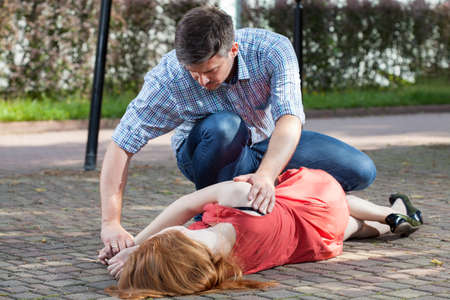 recovery position: Man lying unconscious girl in recovery position