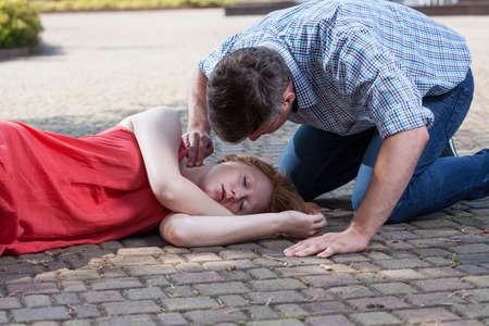 recovery position: Adult man checking pulse of fainted girl Stock Photo