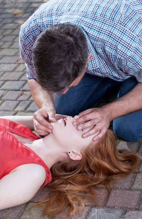 Adult man doing artificial respiration young woman photo