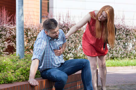 chest pain: Young woman want to help man with chest pain Stock Photo