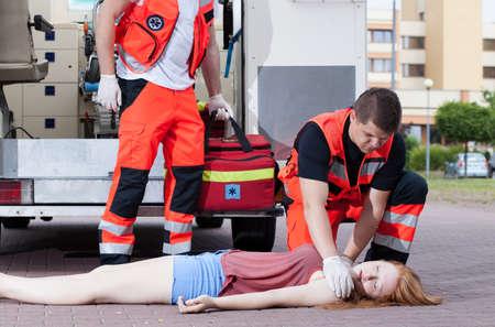paciente en camilla: Dos paramédicos que aplican los primeros auxilios chica inconsciente Foto de archivo