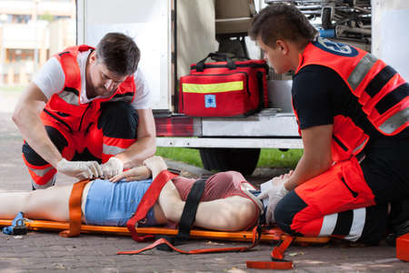 Horizontal view of senseless woman lying on stretcher