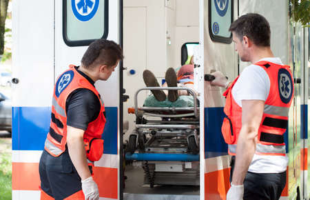 go inside: Image of woman lying on stretcher in ambulance Stock Photo