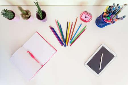 niños estudiando: Vista superior de cuaderno abierto, creyones del lápiz y la tableta en el escritorio blanco Foto de archivo