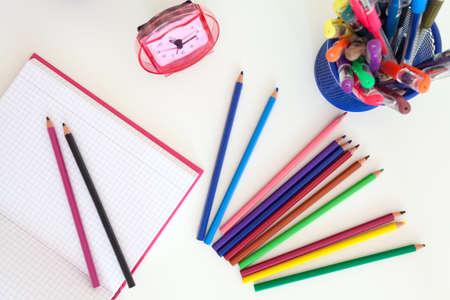 Strumenti per i bambini della scuola sulla scrivania bianco