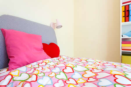 Comfortable bed with colorful bedding in little girl room photo